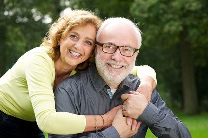 Hugging middle-aged couple posing outdoors
