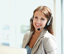 Young brunette business woman with a telephone headset on.