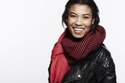 A beautiful young woman wearing a black leather jacket and a huge scarf smiles happily.