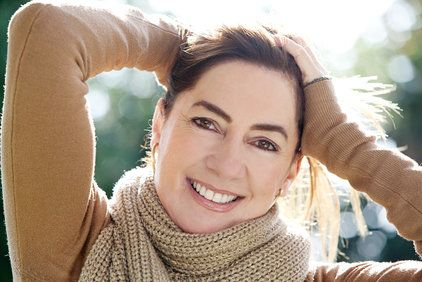 Smiling woman wearing a beige scarf