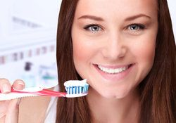 A young woman smiling with a toothbrush full of toothpaste