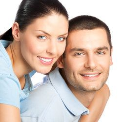 A man and woman in an embrace, both smiling and displaying healthy mouths not affected by chronic dry mouth