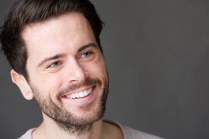 Smiling bearded man in light gray shirt