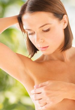Woman with brunette bob lifting arm and looking down at breast