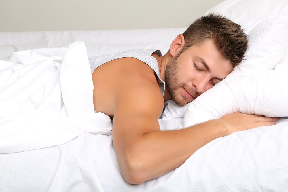 Photo of young man sleeping comfortably on bed with white sheets