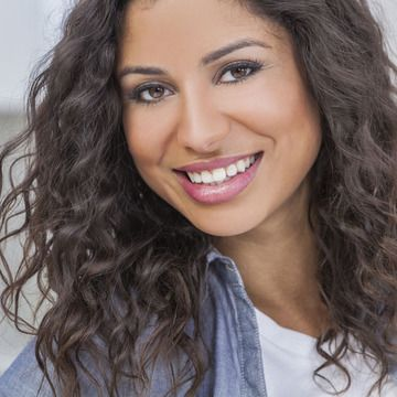 Smiling woman with long, curly brown hair