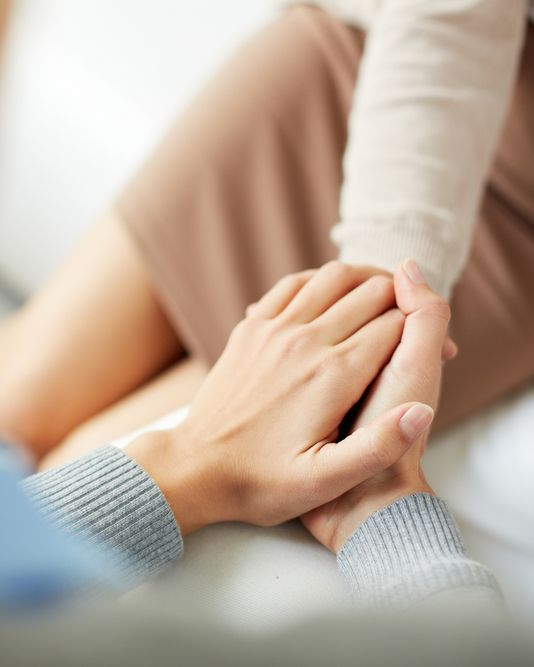 A fertility specialist clasping hands with a patient while discussing miscarriage symptoms