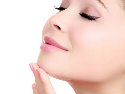 Closeup of a woman touching her chin with her fingertips