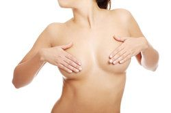 nude woman covering her breasts with her hands