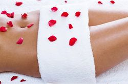 Woman's slim, toned torso covered with spa towel and rose petals