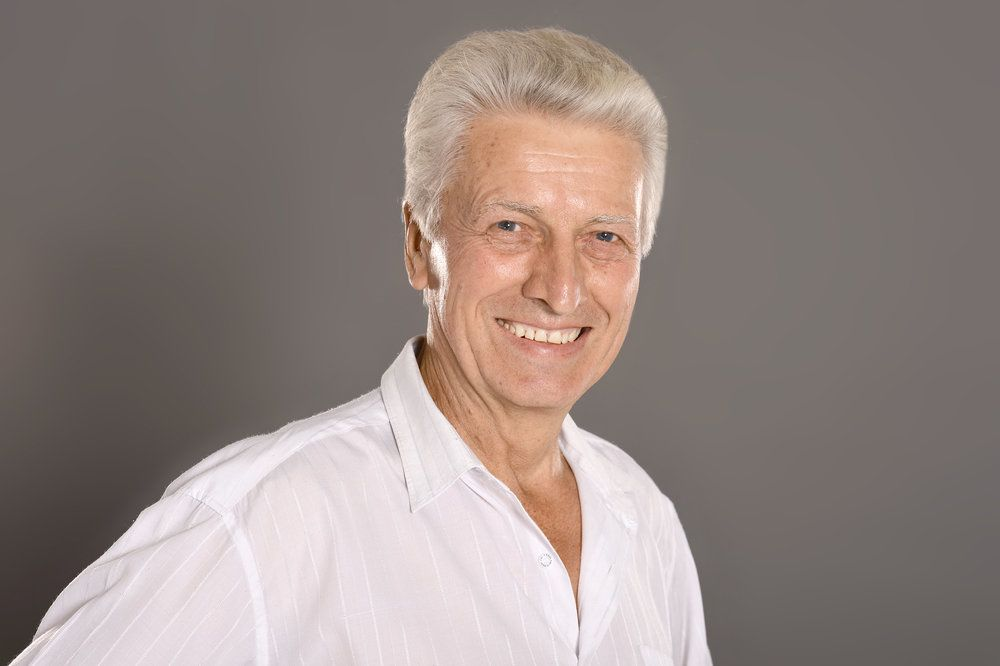 A grey-haired man smiling to reveal his natural-looking dental implant-supported dentures