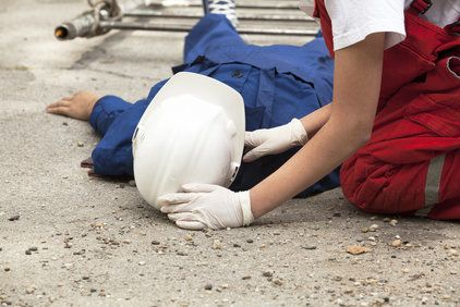 Injured construction worker lying on his back and receiving care