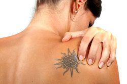 Woman clutching sunburst tattoo on her shoulderblade