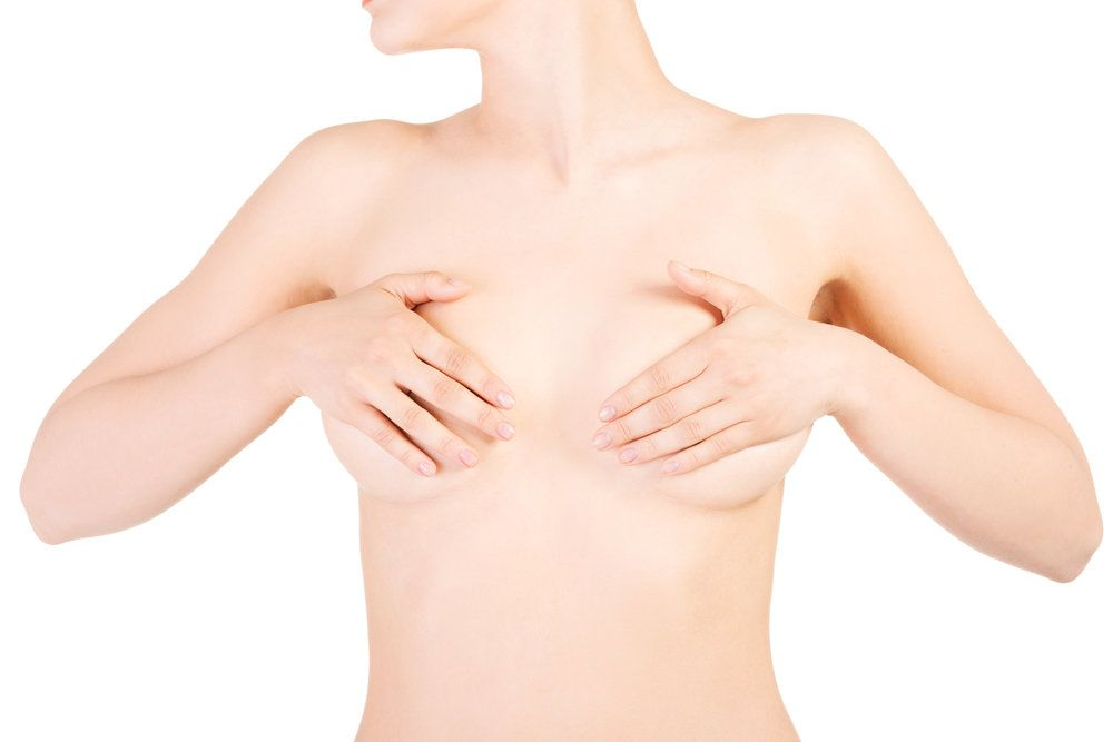 Pale woman covering naked breasts with hands