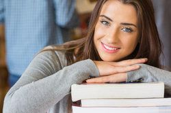 Close up portrait of a smiling female student with stack of books at the college library