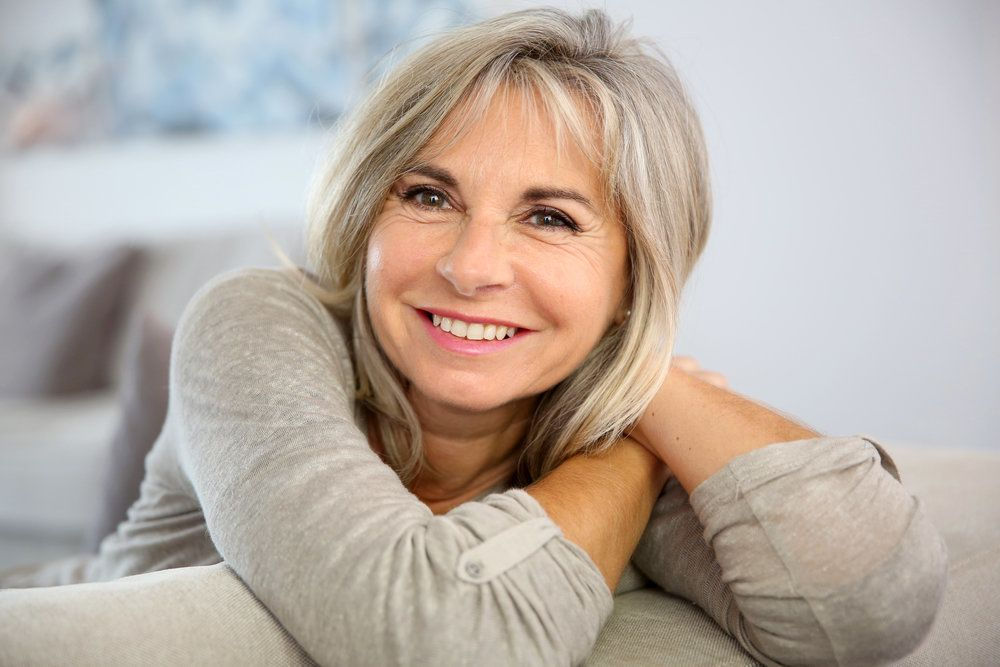 Smiling middle-aged woman relaxing and leaning over side of couch with arms crossed