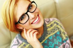 A young woman in glasses smiling