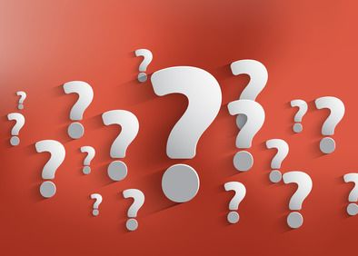 Several white question marks of different sizes positioned on a red background.