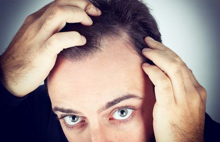 A close-up view of a man looking carefully at his hairline.