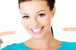 Young woman with white teeth on white background.