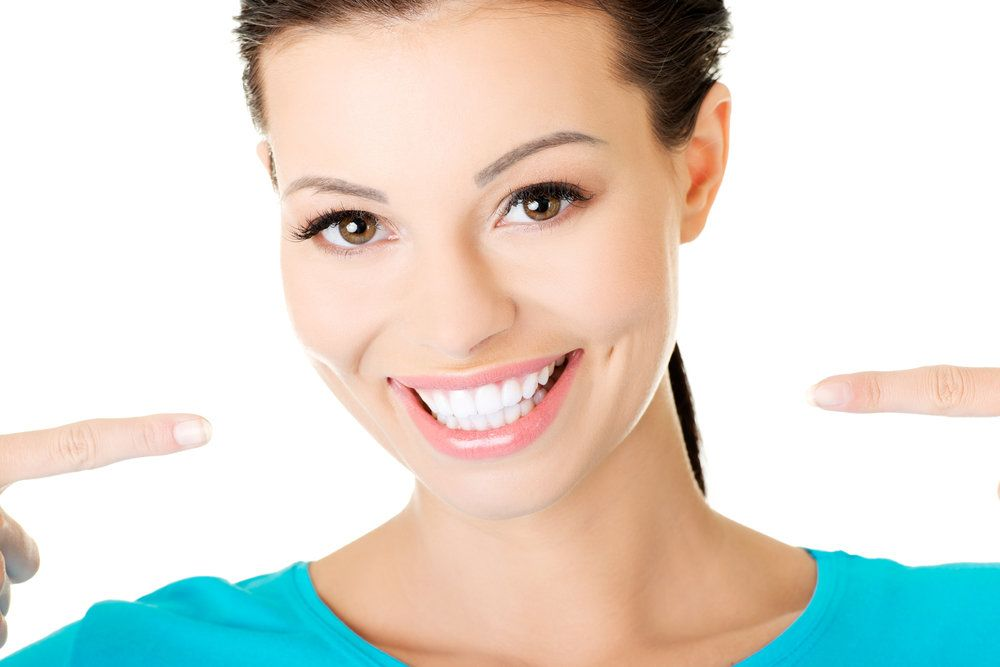 Woman pointing to her white smile.