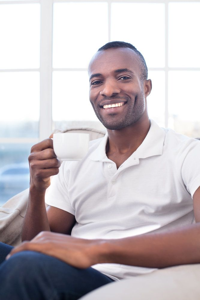 Man with a white smile holding a cup of coffee