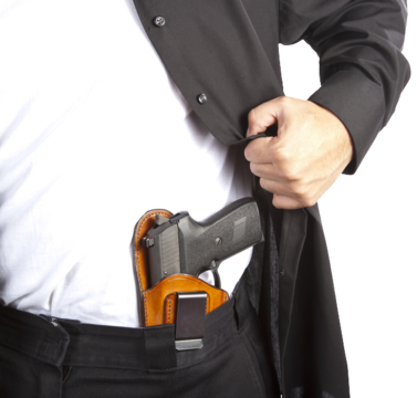 Man in black pants showing gun tucked in waistband