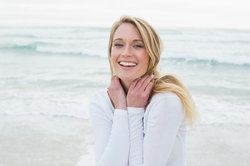 A beautiful woman with blonde hair wearing a white long-sleeved shirt smiles joyfully on the beach.