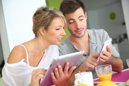 A young couple looks at their phone and tablet with interest.