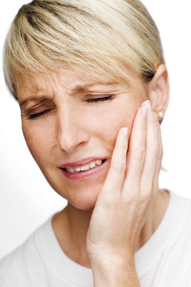A woman clutching her jaw in pain due to a root canal infection