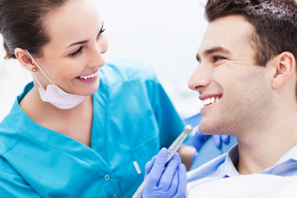 A female dental assistant looking in the mouth of a smiling male patient.