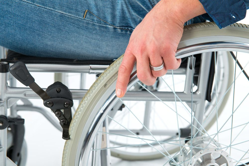 Close up of a man's hand on the wheel of a wheelchair