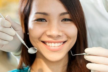 A closeup of a young woman's face with a dentist holding a mirror and dental pick in front of her.