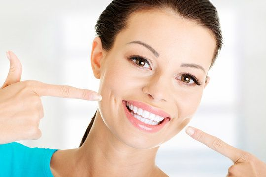 Woman pointing at her straight, white teeth