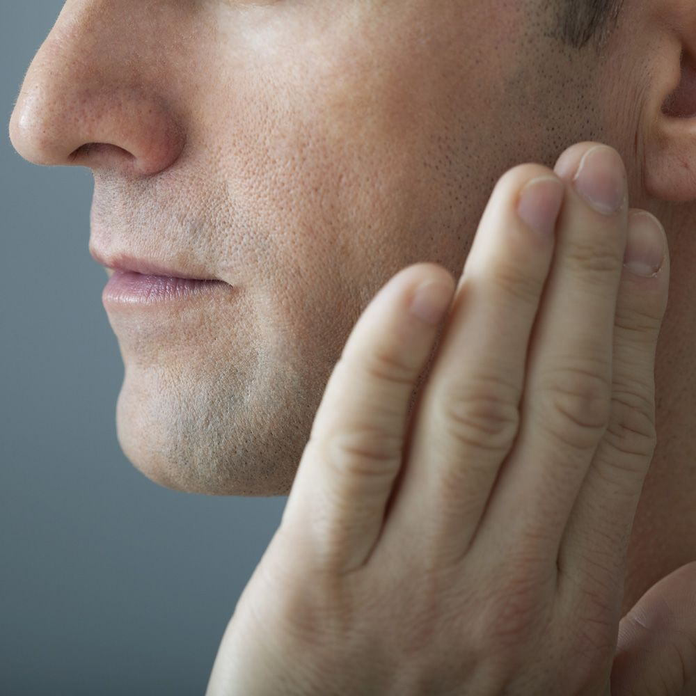 A person with jaw pain and tooth sensitivity