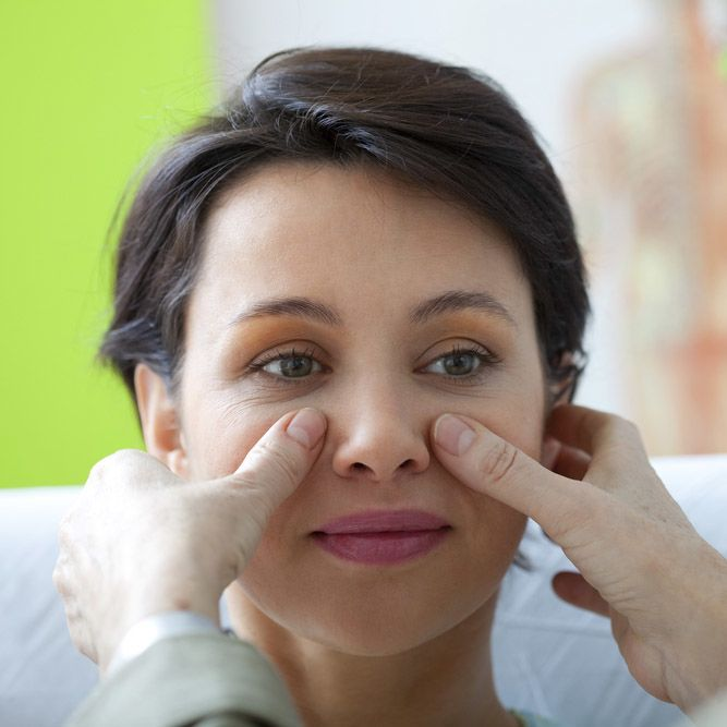 A woman being examined during a rhinoplasty consultation