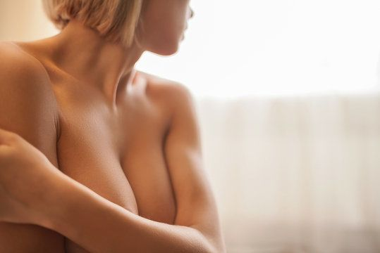 Naked blond woman clutching breasts tightly to her chest