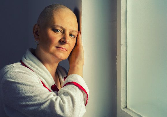 Bald woman suffering from cancer standing in front of the hospital window.