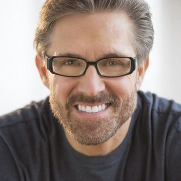 Smiling man with beard and thick-framed glasses