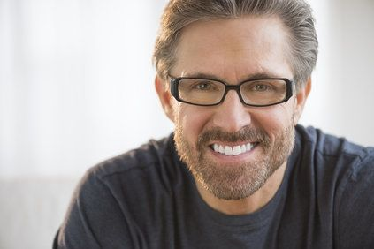Bearded man with black framed glasses smiling