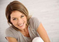 Smiling woman holding folded knees against chest