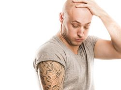 Grimacing man holding head and looking at large tattoo on his arm