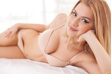 Coyly smiling woman in underwear lying on her side in bed