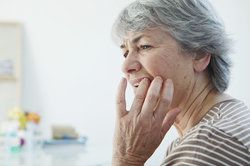 Elderly woman holding jaw in pain and touching tooth