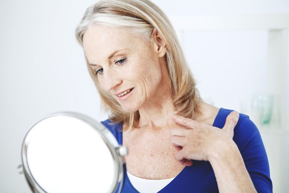 An older woman examines her neck in a mirror