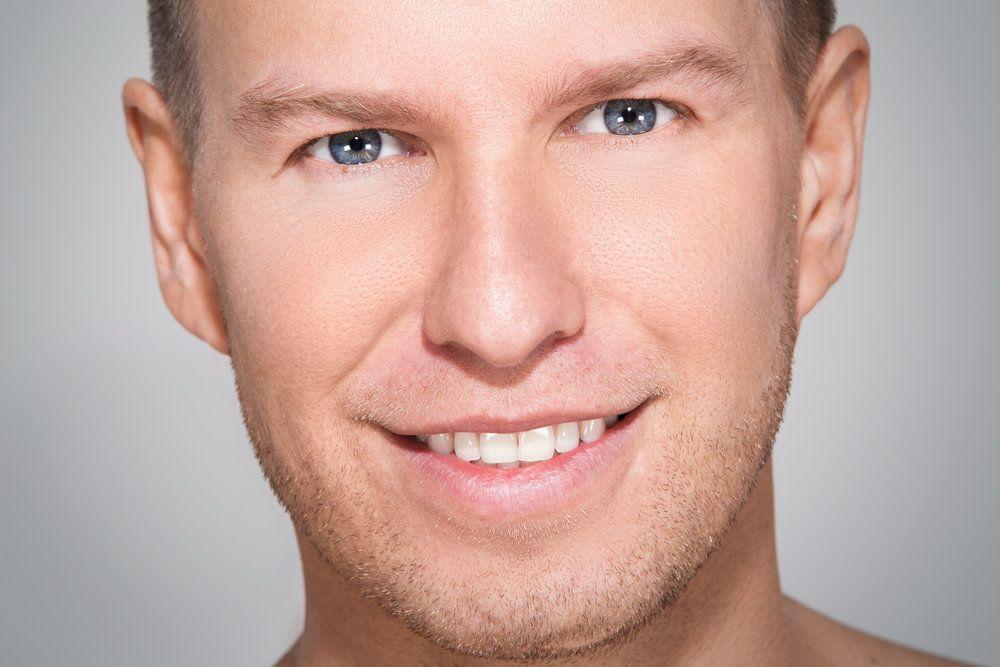 A man smiling, his facial skin smooth after facial plastic surgery