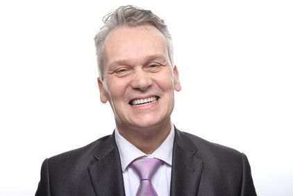 Smiling man in suit and lilac tie