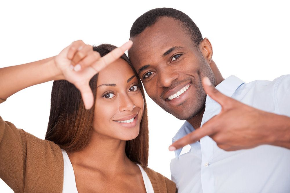 Smiling couple holding heads together and using fingers to mimic photo frames