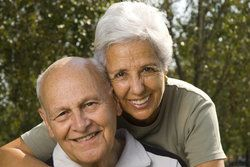 Elderly Caucasian couple smiling and hugging, with full set of attractive teeth