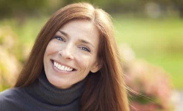 Smiling red-headed woman wearing gray turtleneck